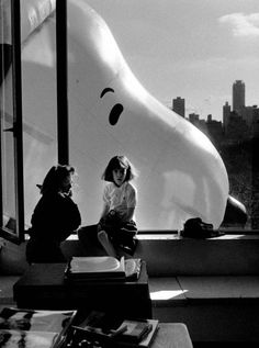 Snoopy Balloon goes by window with young girl sitting on the ledge