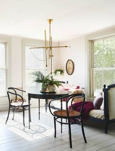 i cannot handle how chic this dining room is. love the gold chandelier, the antique daybed, those black and cane chairs. love love love.