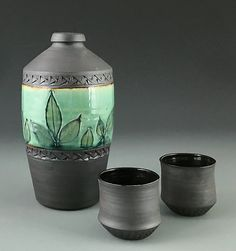 Wheel thrown stoneware sake bottle and two cups with botanical imprint on bottle glazed in copper celadon. Sake Set by Suzanne Crane