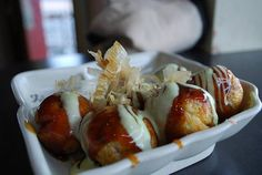 Takoyaki is a popular Japanese street food. It's basically a ball of crisp wheat batter with a sweet chunk of octopus meat inside. It is topped with bonito flakes (dried fish) or doused in mayonnaise. If you are a seafood-lover you'll definitely need to try this whenever you're in Japan.