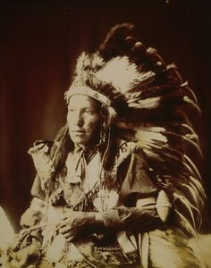 Bad Wound, Sioux, wearing war bonnet, 1899