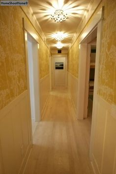 Designer: Ally Kim / Kws: narrow hallway vista decor design decorating ideas diy lighting light.  Lower wall wainscoting, toile/damask wallpaper above, soft contrast, repetition of lighting.