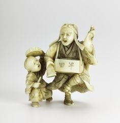 Netsuke of carved ivory, a dancer with a fox mask on his back accompanied by a small boy with a drum: Japan