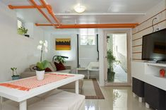 Love the pop of orange !  Refreshing way to handle a basement apartment - white walls, white ceilings, brightly painted pipes as minimal art.