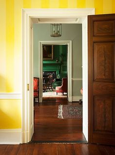 The view from the sunshine-yellow sitting room into the deep emerald-green library.