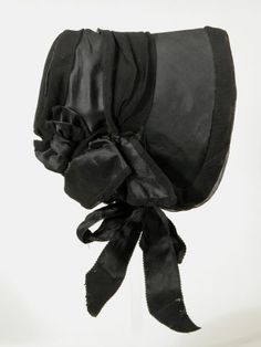 Mourning bonnet, 1840-1845. Material unspecified but possibly silk and velvet bonnet with wide ribbon band and folded rose decoration on the side, and black ribbons to tie under the chin. From the National Trust collection at Snowshill.
