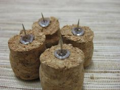 Idea » Cork Thumbtacks » Drill a hole in the cork for the thumbtack, hot glue the bottom, and insert thumbtack into the cork.