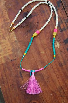 Pink silk tassel with various beads including African vinyl.  Clasp in back  28 inches long