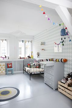 The neutrals in the wallpaper and dresser are the perfect backdrop for modern child's furnishings and accessories.