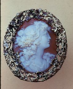 ANTIQUE CAMEO BROOCH~ Woman in profile coiffed in flowers, set in a 14k gold intricately designed grape and vine motif frame.