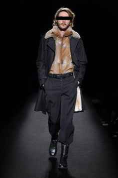 Fur trench coat worn with a sleeveless fur camionneur lining jacket, wool wide leg trousers, a leather belt and 'Replica' leather biker boots.