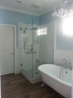 Relaxing - Frameless shower door, clawfoot tub, carrara marble seat, curb and shower niche, white subway tile. Love the relaxing blue wall paint from PPG.
