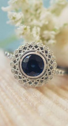 This vintage-inspired halo engagement ring is stunning with a sapphire center stone.