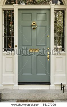 Front entrance to a home with classic design. The door has a large brass knocker and an elegant frame. Vertical shot. by Portlandia, via Shu...