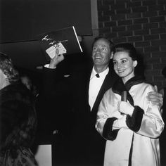 "The actress Audrey Hepburn photographed with her husband Mel Ferrer (actor, dialogue coach and film director) during their arrival for the premiere of ""Suddenly Last Summer"" (directed by Joseph L. Mankiewicz) in Beverly Hills, California (USA), on..."