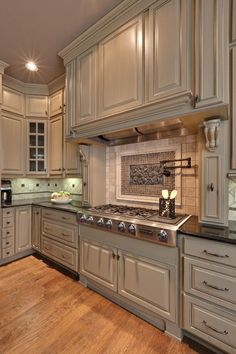 Glossy greige cabinets complement this kitchen's lightly stained flooring. Paint Pick: Tapestry Beige OC-32 by Benjamin Moore
