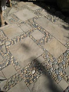 steingarten mit natursteinplatten und kieselsteinen