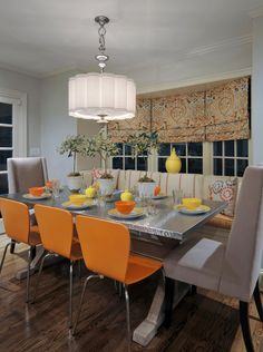 orange chairs, grey chairs, orange/grey/yellow fabrics, stainless steel top farm table, large shade chandelier