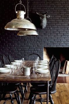 black painted brick | modern farmhouse dining room | long wooden and industrial pipe table with black chairs