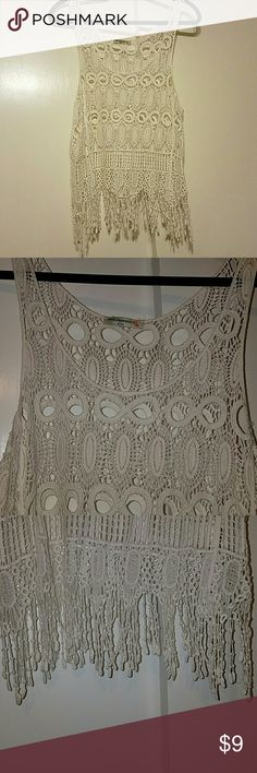 Cute white lace crochet top This is a cute top. See through white crochet top. Dangling knitted strings on the bottom. brand Tops