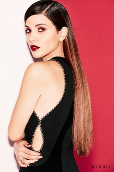 Negin Mirsalehi wears a deep copper eye shadow and deep red lip color