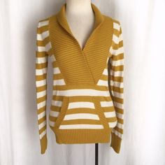 """Fossil Yellow & White Stripe V-Neck Sweater Mid-weight, cozy deep v-neck sweater from Fossil. This is a mustard yellow that looks great layered over chambray/denim, black, gray! Ribbed collar, cuffs, and hem with a kangaroo pocket in front. 60% cotton; 25% modal; 15% angora rabbit hair. Machine washable. Size Small. Bust: 16.5"""" flat across. Waist: 15"""" across. Length: 26""""  Shoulder to shoulder: 13.5"""" There is some very minor pilling but it is sparse and easily removable. Overall EUC. Thanks…"""
