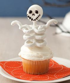 For each skeleton, carefully thread the stick end of the marshmallow head through the small hole of a pretzel, slowly twisting the pretzel from side to side as you push it up toward the head, stopping about 1⁄2 in. below the head. Secure the pretzel in position with a dab of frosting. Add 2 more pretzels, lining them up, to resemble the rib cage, securing with dabs of frosting. Stick the skeleton into the top of a cupcake. To make the arms, carefully cut a pretzel in half with a serrated kni...
