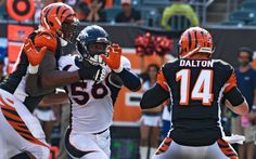 Denver Broncos outside linebacker Von Miller (58) has his eye on on Cincinnati Bengals quarterback Andy Dalton (14) during the fourth quarter but is held by Cincinnati Bengals offensive tackle Cedric Ogbuehi (70) on the play September 25, 2016 at Paul Brown Stadium. John Leyba, The Denver Post