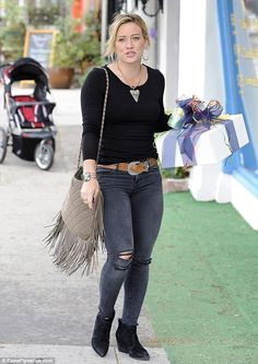 Edge: Hilary kept it rocker chic in a black top, faded black skinny jeans ripped at the kn...