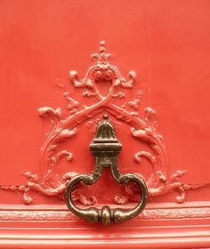Close-up of what appears to be a drawer pull on a salmon-pink painted piece of furniture.