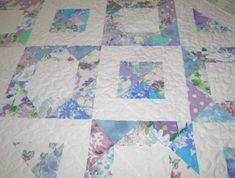 This fresh looking quilt, made entirely of vintage sheets in varying hues of blues, mauves and greens, will brighten the remainder of your winter days and take you sailing into spring! The front is pieced using half square triangles to create squares, each made up of a combination of a floral print and a solid white, then pieced together so that they form a series of diamonds. The double fold binding is machine stitched to the front of the quilt and then neatly hand stitched to the back…