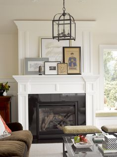 lantern-style light fixture, asymmetrical art arrangement on mantel, dark wood sideboard...I'd love a more colorful rug, wallpaper, and different upholstery on the x-stools