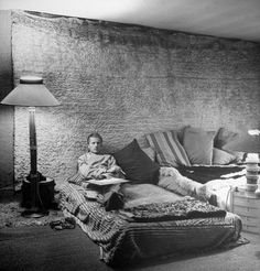 Composer and writer Paul Bowles, lying in bed with his paper and pen.