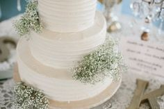 A little bit of baby's breath makes a big impact on a white wedding cake.
