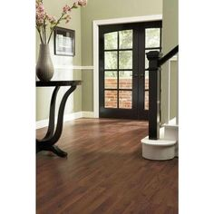 This laminate flooring with white trim, dark espresso wood accents, and green walls!