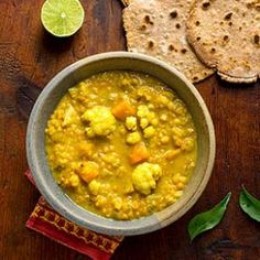 Winter Vegetable Dal Recipe with coconut oil, brown mustard seeds, cumin seed, bay leaf, fresh curry leaves, onions, serrano chile, fresh ginger, garlic, water, red lentils, lite coconut milk, salt, ground turmeric, butternut squash, cauliflower florets, yukon gold potatoes, garam masala, lime juice