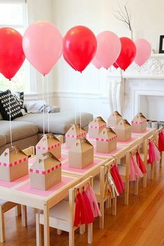 Favor box's with attached balloons on a string.