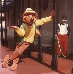 Br'er Fox on Main Street prior to the Park opening at Disneyland in the 1970s. The 'miniature' policeman is actually Mickey Mouse without his head. (You can see Mickey's distinctive pants and suspenders.)