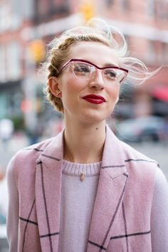 Gorgeous deep red lipstick with matching cateye eye glasses frames, windswept French braid halo with face-framing wisps, delicate gold jewelry, sleeveless pink plaid duster and pale pink crewneck sweater.