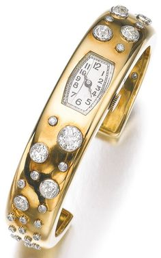 Lady's gold and diamond cocktail watch, Suzanne Belperron, 1943. Set at the centre with a tonneau shaped dial applied with Arabic numerals, within a gold cuff highlighted with circular- and single-cut diamonds, French assay and maker's marks for Groëné &