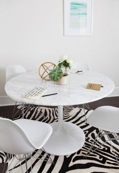 A marble-topped Saarinen table is the site of our editorial meetings and brainstorm sessions. (Art from Minted // zebra cowhide rug and brass sculpture from West Elm.)
