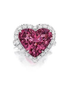PURPLE SPINEL AND DIAMOND RING, NISAN. Centring on a heart-shaped purple spinel weighing 9.29 carats, to a stylised mount decorated with brilliant-cut diamonds extending to the shoulders, the diamonds together weighing approximately 1.35 carats, mounted in 18 karat white gold, signed. Ring size: 5¼