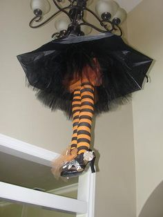 Umbrella, tulle & stockings hanging in the entry way. Such a cute Halloween decoration