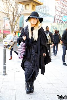 Ootsubo is a Bunka Fashion College student – with blonde and all black fashion – who me wet on the streets of Harajuku. Ootsubo is wearing a Bernhard Willhelm coat over a resale dress and cardigan. She is also wearing a statement chain and tassel necklace, floppy hat, printed tote bag and spiked Jeffrey Campbell studded Litas. (Tokyo Fashion, 2014)