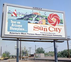 Billboard advertising Sun City in the Tour an Arizona Showplace. Del Webb's Sun City, Equal Housing Opportunity, America's Most Famous Resort-Retirement Community. This was near Grand Avenue, notice the Peoria water tower is in the background Sun City Arizona, Grand Homes, Enjoying The Sun, Water Tower, Billboard, Community, Tours, America, Activities