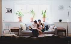 A photojournalistic photograph of a family sitting on the couch during an in home family photo session in Jamaica Plain - Boston, Massachusetts - Gina Brocker Photography