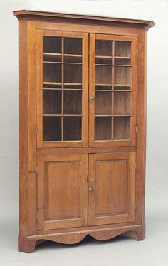 An American Cherrywood Corner Cupboard, c. 1820, Port Gibson, Mississippi, the architectural stepped molded cornice over mullion glazed doors enclosing original shelves flanked by canted corners, the cupboard doors enclosing a shelf, scalloped skirt raised on bracket feet, height 93 in., width 57 in. Antique Corner Cabinet, Corner Cupboard, Cupboard Doors, Furniture Styles, Antique Furniture, Painted Furniture, Southern Furniture, Country Furniture, Corner Cabinets