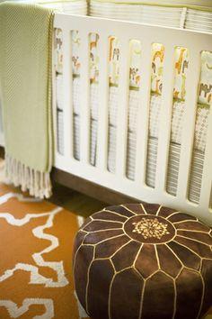 Beautiful nursery design with West Elm Iznik Dhurrie Rug in Sorrel, white modern crib, Serena & Lily Tan Moroccan Leather Pouf and green herringbone throw blanket.