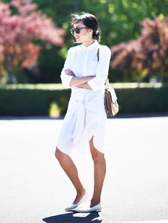 A shirtdress with a faux waist tie is worn with white flats and a shoulder bag.