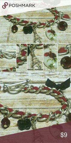"""**NEW**Paris Inspired Charm Bracelet 7.5"""" Silvertone chainlink with toggle clasp closure. Red ribbon woven through out. Has a series of charms on including the Eiffel Tower. Jewelry Bracelets"""